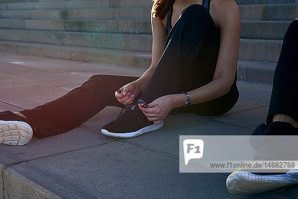 Frau bindet Schnürsenkel an Stufen im Sportstadion
