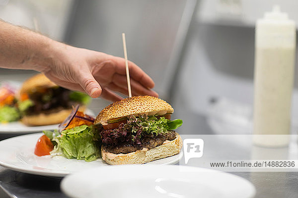 Fast food worker preparing hamburger and salad in commercial kitchen  close up of hand
