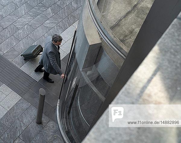 Geschäftsmann mit Rollgepäck wartet auf den Aufzug