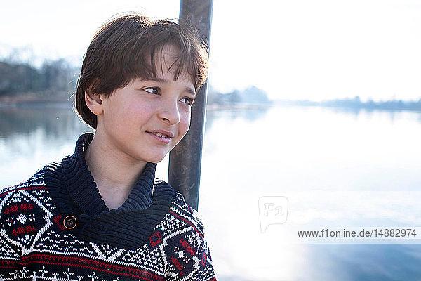 An einen Pfahl am See gelehnter Junge  Porträt  Comer See  Lecco  Lombardei  Italien