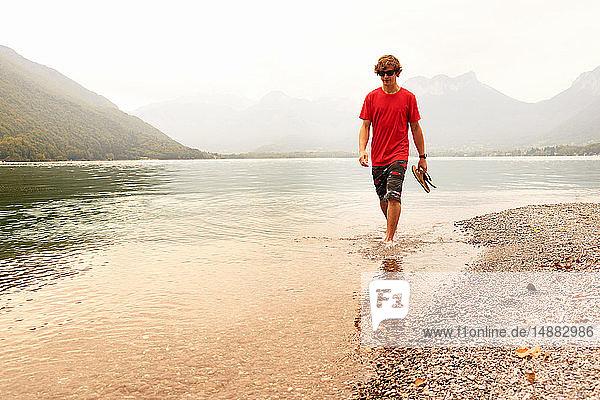 Junger Mann paddelt knöcheltief im See von Annecy  Annecy  Rhône-Alpes  Frankreich