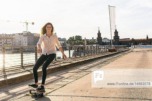 Junge Frau beim Skateboarden auf Brücke  Fluss und Gebäuden im Hintergrund  Berlin  Deutschland