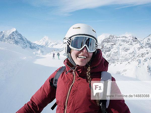 Junge Skifahrerin mit Helm und Skibrille lächelt in schneebedeckter Landschaft  Porträt  Alpe Ciamporino  Piemont  Italien