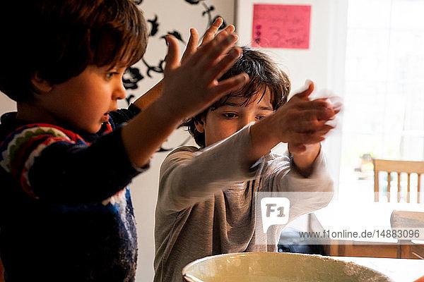 Jungen spielen mit Mehl in der Rührschüssel