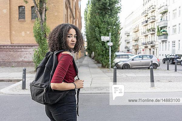 Junge Frau mit Rucksack auf der Straße  Berlin  Deutschland