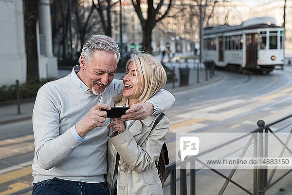 Senior couple using smartphone on sidewalk in city