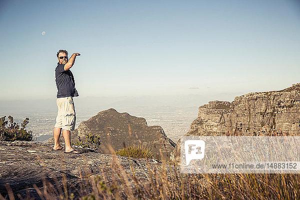 Reifer Mann im Rückblick von einer erhöhten Felsformation  Porträt  Kapstadt  Westkap  Südafrika
