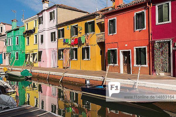 Moored boats on canal lined with pink  red  orange  yellow and green stucco houses decorated with curtains  washed clothes on clothesline  Burano Island  Venetian Lagoon  Veneto  Italy