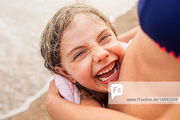 Lachendes Mädchen wird von Mutter am Strand umarmt  Portoferraio  Toskana  Italien
