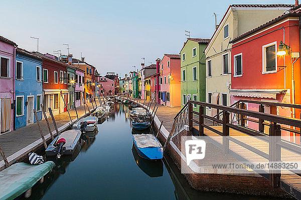 Verankerte Boote auf einem Kanal mit farbenfrohen Stuckhäusern  Geschäften und Fußgängerbrücke in der Abenddämmerung  Insel Burano  Venezianische Lagune  Venedig  Venetien  Italien