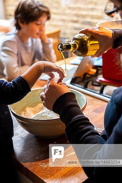 Kleinkind hilft Mutter  Öl in Mehl in Rührschüssel zu gießen