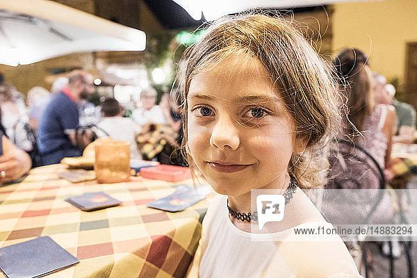 Mädchen am Restauranttisch sitzend  Kopf- und Schulterportrait