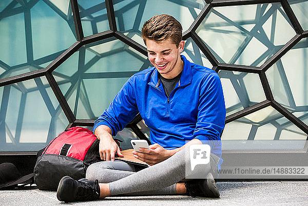 Junger Mann benutzt Smartphone an Glaswand  London  UK