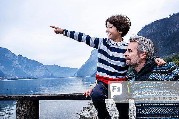 Junge und Vater zeigen vom Pier am Seeufer  Comer See  Onno  Lombardei  Italien