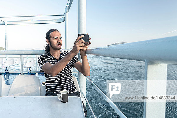 Man on cruise boat taking photograph