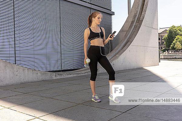 Junge Frau macht Pause vom Sport und benutzt Smartphone in der Stadt  Berlin  Deutschland