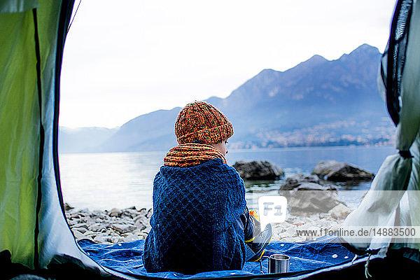 Junge sitzt auf einer Decke am Zelt  Rückansicht  Comer See  Onno  Lombardei  Italien