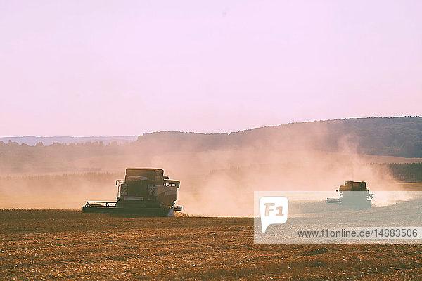 Combine harvesters harvesting dusty wheat field