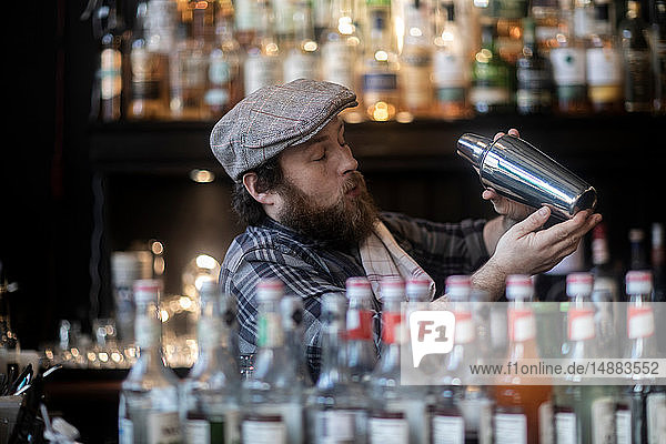 Barman shaking cocktail in traditional Irish public house