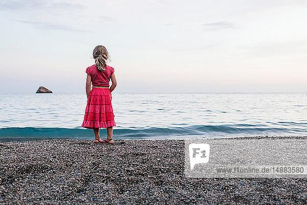 Mädchen in rotem Kleid beobachtet das Meer vom Strand aus  Rückenansicht  Portoferraio  Toskana  Italien