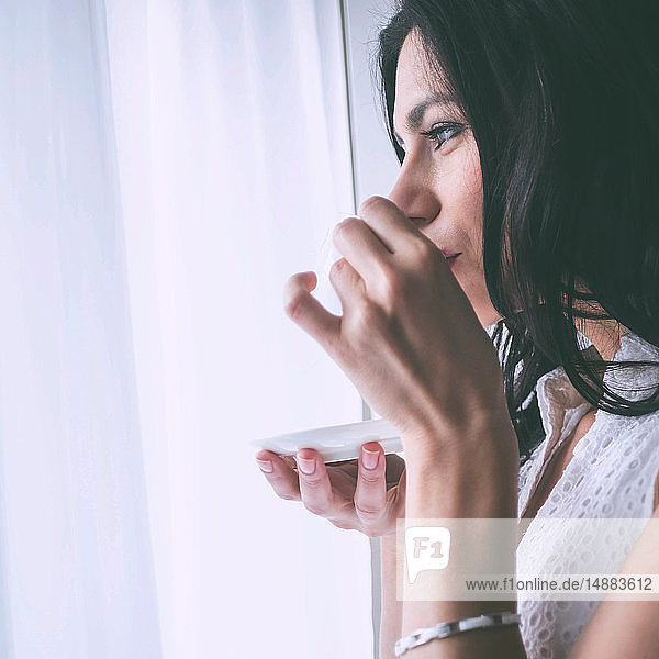 Woman drinking coffee beside window