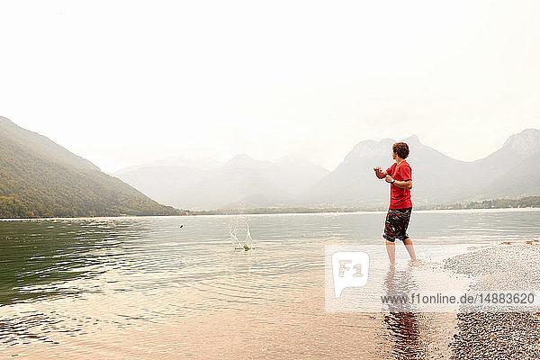 Junger Mann beim Steinschleifen im See von Annecy  Annecy  Rhône-Alpes  Frankreich