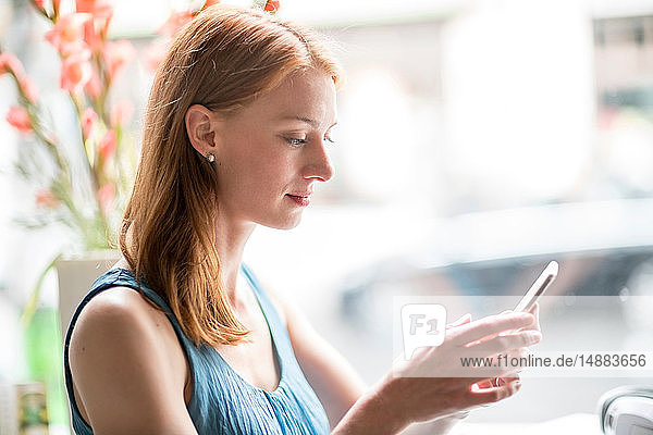 Frau benutzt Smartphone im Büro