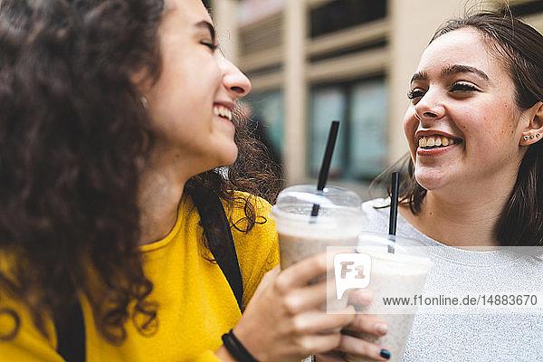 Freundinnen stoßen im Freien mit Smoothie an
