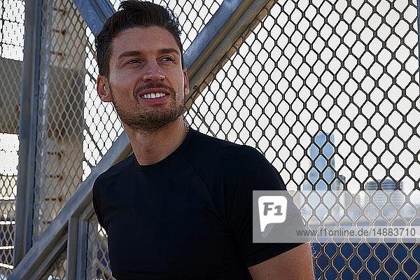 Mann macht Pause neben eingezäunter Mauer im Sportstadion