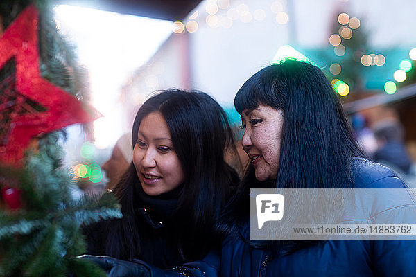 Mother and daughter window shopping at Christmas market  Freiburg  Baden-Wurttemberg  Germany