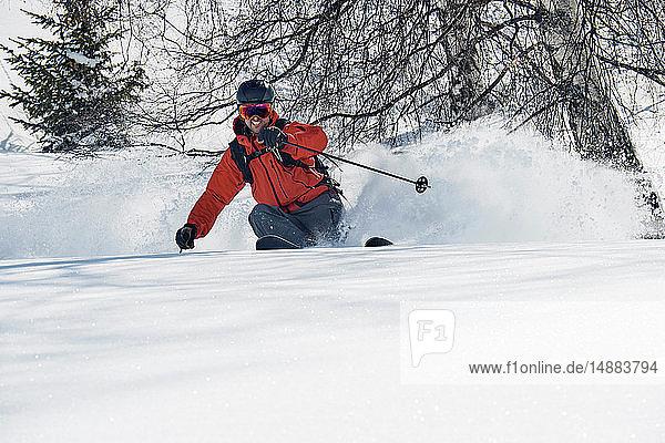 Männlicher Skifahrer beim Skifahren am Berghang  Blick aus niedrigem Winkel  Alpe-d'Huez  Rhône-Alpes  Frankreich