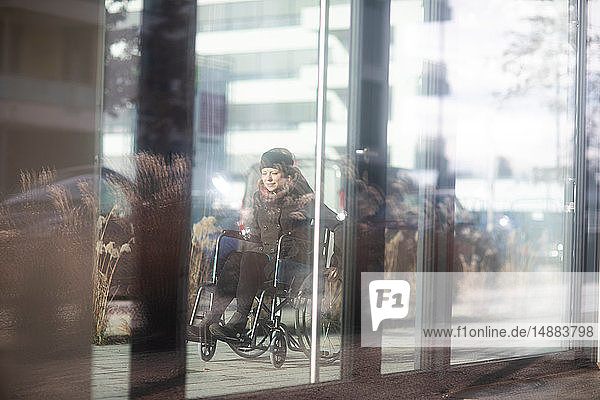 Reflection of woman in wheelchair on glass windows of building