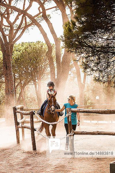 Mutter führt Reitertochter im Paddock,  Portoferraio,  Toskana,  Italien