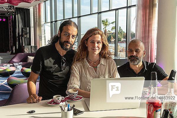 Gruppe von drei Unternehmern  die einen Laptop benutzen und Kaffee im Büro trinken