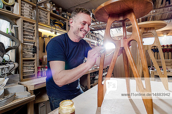 Craftsman polishing wooden stool with oil finish