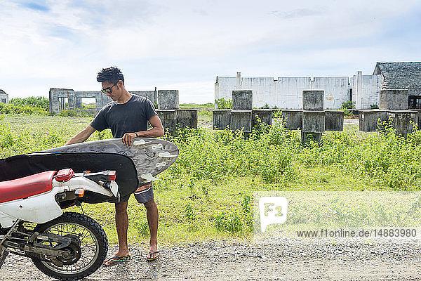 Motorradfahrer mit Surfbrett  Abulug  Cagayan  Philippinen