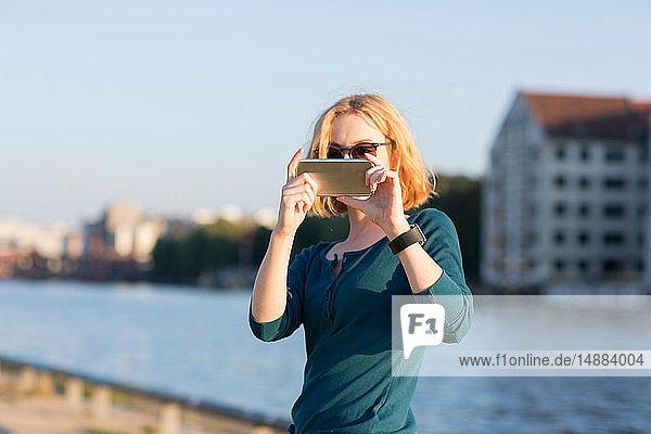 Junge Frau fotografiert mit einem Smartphone am Fluss im Sommer  Berlin  Deutschland
