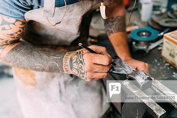 Axtmacher mit Stahlschleifer in der Werkstatt Axtmacher mit Stahlschleifer in der Werkstatt