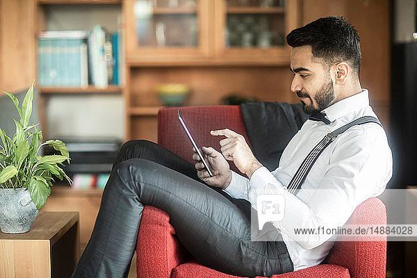Geschäftsmann mit digitalem Tablett im Sessel