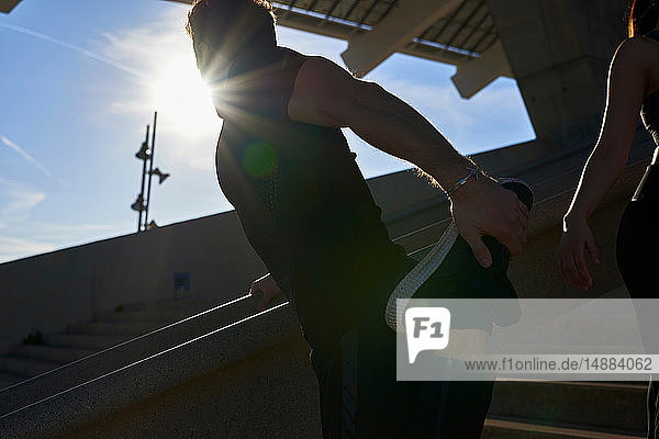Mann streckt sich auf Stufen im Sportstadion