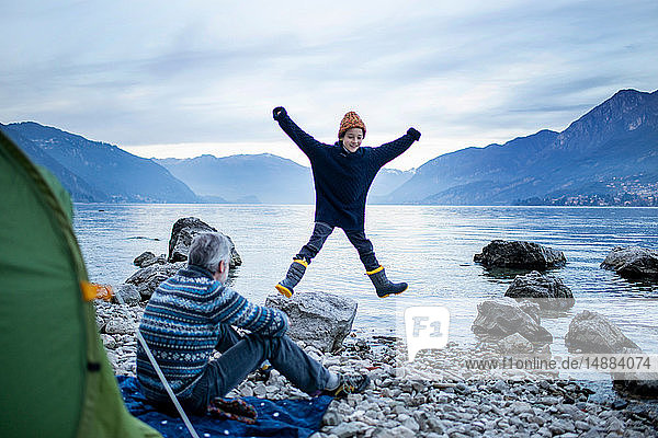 Vater beobachtet Sohn beim Sternensprung am Seeufer  Onno  Lombardei  Italien