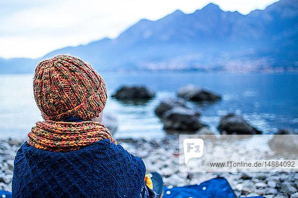 Junge sitzt auf einer Decke am Seeufer  Rückansicht  Comer See  Onno  Lombardei  Italien