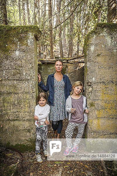 Frau und zwei Töchter stehen in einer verlassenen Türöffnung im Wald  Sandpoint  Idaho  USA