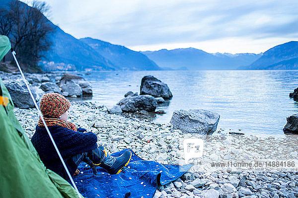 Junge sitzt vor dem Zelt am Seeufer  Comer See  Onno  Lombardei  Italien
