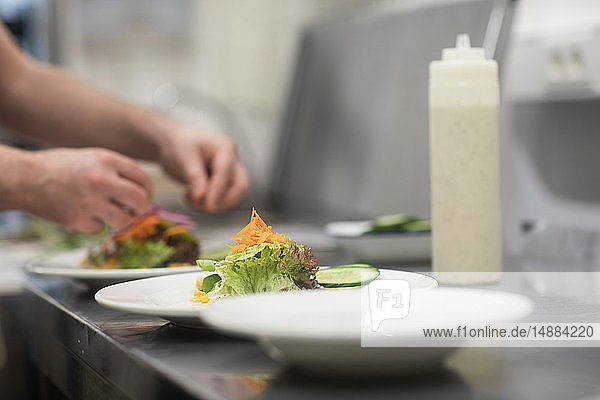 Fast food worker adding salad to hamburger in commercial kitchen  detail of hand