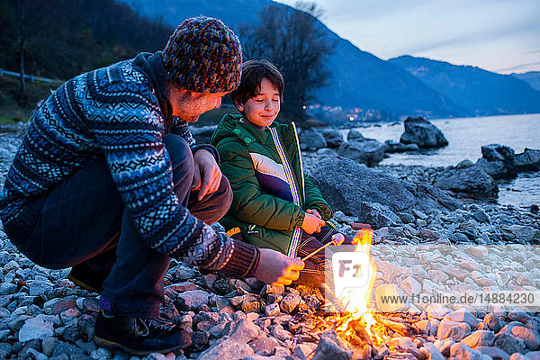 Vater und Sohn toasten Marshmallows über dem Lagerfeuer  Onno  Lombardei  Italien