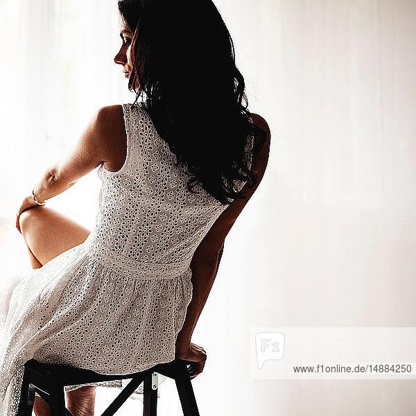 Frau im Sommerkleid auf Barhocker