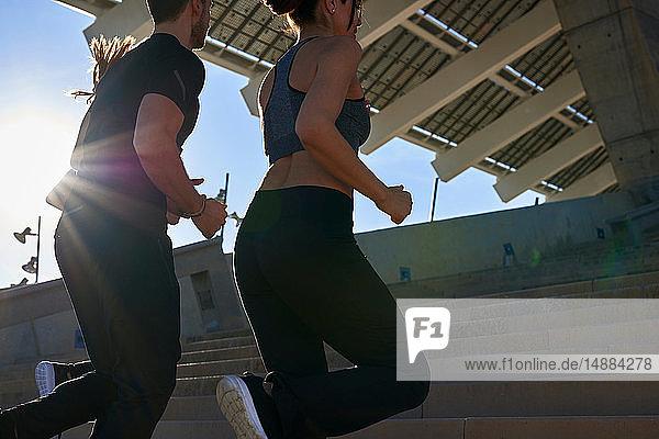 Freunde joggen Treppenstufen im Sportstadion hoch