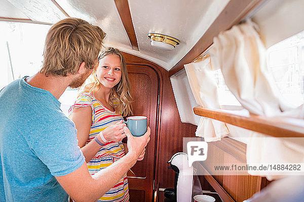Junges Paar in Segelbootkabine beim Kaffee kochen