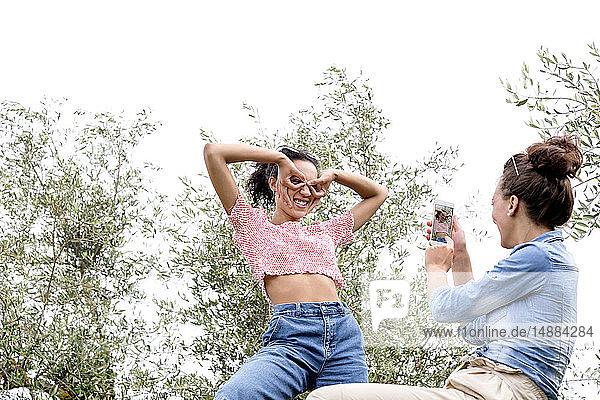 Frau fotografiert einen Freund  der Gesichter schneidet